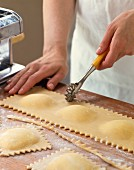 Ravioli being cut with a pastry wheel