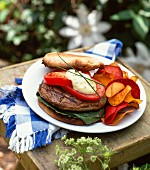 A veggie burger and vegetable crisps on a wooden board in a garden