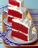Three slices of Red Velvet cake on plates (USA)