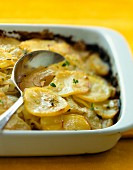 Potato gratin in a baking dish with a spoon