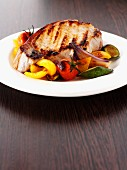 A grilled pork chop with roasted Mediterranean vegetables