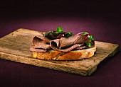 Scheibe Weissbrot mit Roastbeef auf Holzbrett