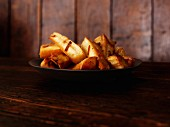 Honey-roasted parsnips on a black plate