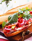 A lavishly topped baguette with ham, salami, cheese and vegetables