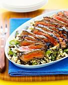 Sliced beef steak on an asparagus and rice salad