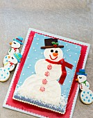 A rectangular cake decorated with a snowman with snowman biscuits