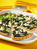 A wholemeal pizza topped with spinach, feta cheese and olives