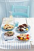 Verschiedene Vorspeisen aus Griechenland: gegrillter Haloumi mit Paprika, Keftedes mit Pitabrot und Tzatziki, marinierter Oktopus, Teigtaschen mit Feta