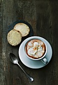 A buttered roll and a cup of hot chocolate with milk foam and cream