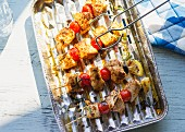 Turkey skewers with tomatoes and olives on an aluminium tray