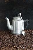 Aluminium-Kaffeekanne und Löffel auf Kaffeebohnen