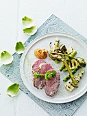 Roast lamb with grilled artichokes, courgettes and asparagus