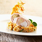 Rabbit roulade with chicory on a bed of risotto garnished with a Parmesan wafer