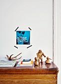 Alter Turnkasten als Ablage für Zeitschriften und Dekofiguren, dahinter mit Masking Tape ein Foto mit Sinnspruch an die Wand gepinnt