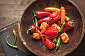 Various chilli peppers and peppers in a wooden bowl