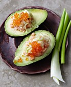 Avocados filled with salmon tartar, caviar and spring onions