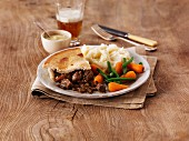 Steak and ale pie with mashed potatoes and vegetables (England)