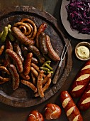 Sausages with gherkins, lye bread rolls, mustard and red cabbage