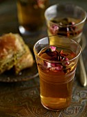 Spiced tea with star anise and rose petals and a baklava in the background