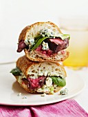 A steak sandwich with spinach and blue cheese