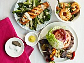 Various barbecue dishes: burger, salmon, prawns, kebabs, asparagus