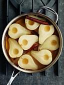 Pochierte Birnen mit Zimtstangen im Kochtopf