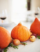 A table decorated for Thanksgiving: pumpkins, onions and rosemary