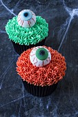 Two cupcakes decorated with sugar eyes for Halloween