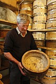 A man holding a wooden mould for making cheese
