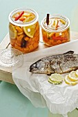 Two jars of sweet and sour pickled pumpkin with grilled trout