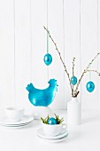 Turquoise Easter decorations and white crockery on a towel against a wooden wall