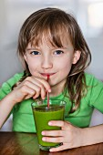 A girl drinking a glass of vegetable juice