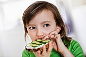 A little girl eating a slice of bread topped with cream cheese and cucumber