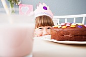 A little girl wearing a crown hiding behind a decorated chocolate cake