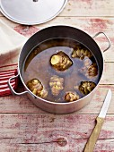 Unpeeled Jerusalem artichokes in a pot of water