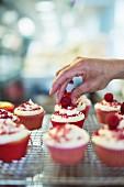 Red Velvet Cupcakes mit Himbeeren verzieren