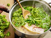 Green kale with pears and smoky bacon being made