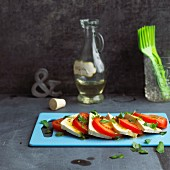 Caprese with tofu on a blue chopping board
