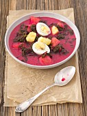Beetroot soup made from roots and leaves with fried potatoes and egg