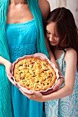 A woman and girl holding a rhubarb crumble cake