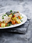 Salmon steak on a bed of root vegetables