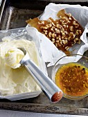 Creamy yogurt ice cream with orange sauce and brittle