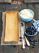 Ingredients for a shortbread tart with mascarpone, white chocolate cream and blueberries