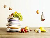 Tellerstapel mit Obst, Gemüse und Pilzen, daneben Ei, Salami und Käse