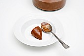 Chocolate cream dumpling with a spoon on a white plate