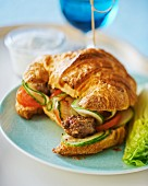 A croissant sandwich with spicy meatballs, cucumber and tomato