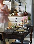 Festliches Buffet mit verschiedenen Häppchen auf rustikalem Holztisch in gemütlicher Küche im Landhausstil