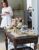 Festliches Buffet mit verschiedenen Häppchen und Tulpenstrauss auf rustikalem Holztisch; im Hintergrund eine essende junge Frau