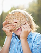 A blond boy hiding behind a crispbread