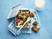 Pasta salad with vegetables and falafel in a lunchbox